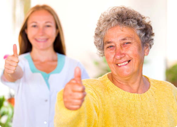 a companion and the elderly showing thumbs up