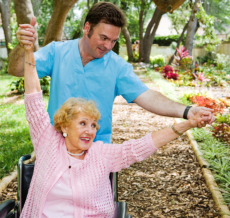 a caregiver man assisting the elderly woman on her physical therapy